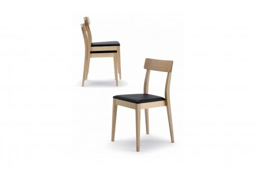 Stohovateľné drevené stoličky Charlotte s koženým sedákom.