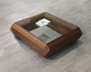 Drevený konferenčný stolík značky Brik so sklom navrchu.